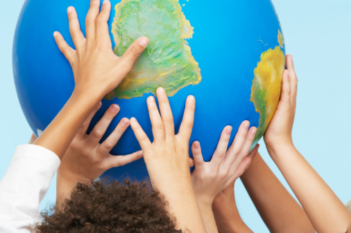 Childrens' hands holding up a globe